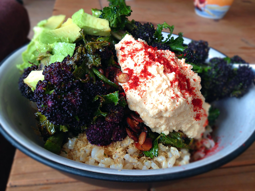 vegan and gluten free Buddha Bowl with avocado, short grain brown rice, hummus and purple sprouting broccoli