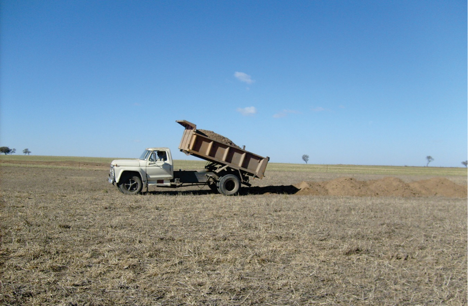 Pequeño camión volcador rellenando una vía de desagüe anulada en la sistematización.
