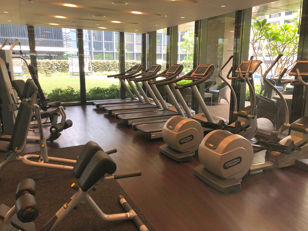 Gym while looking out at the open spaces and swimming pool