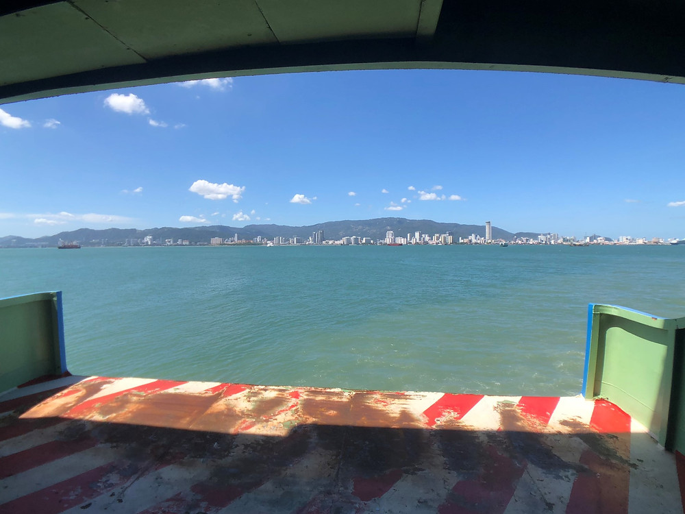 Standing at the front of the ferry looking at Penang Island