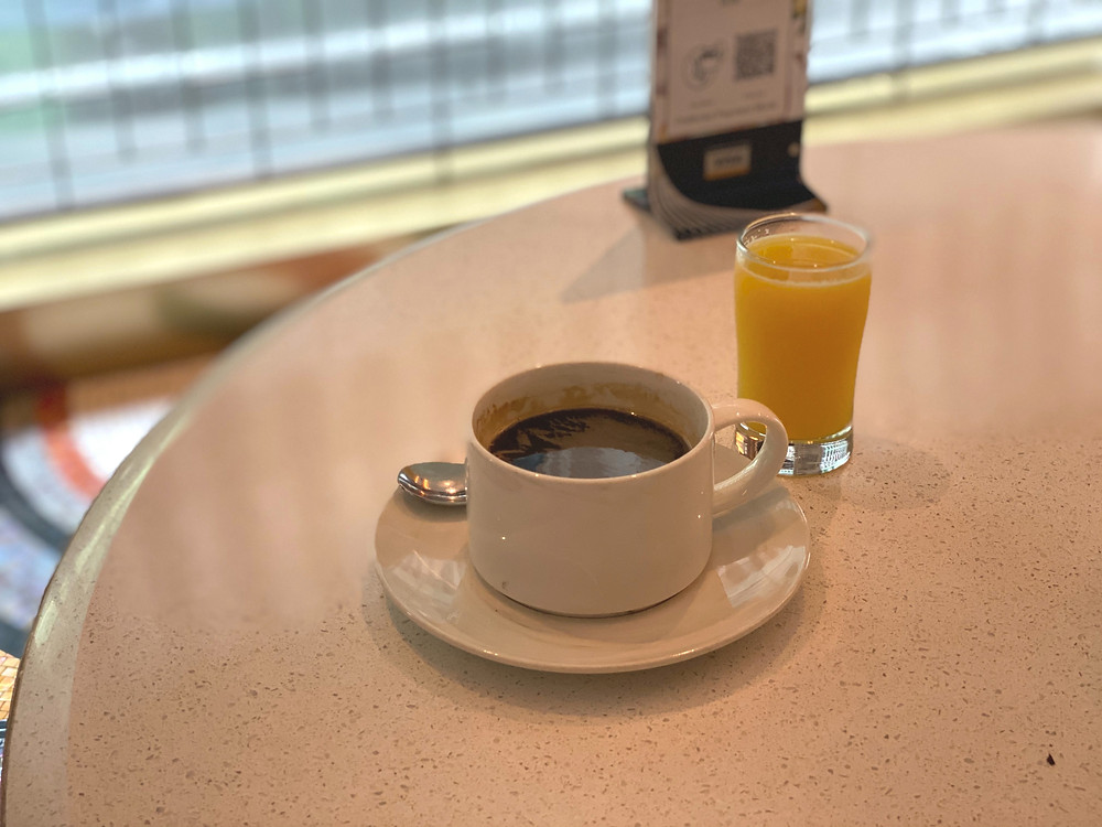 A cup of coffee and a cup of OJ