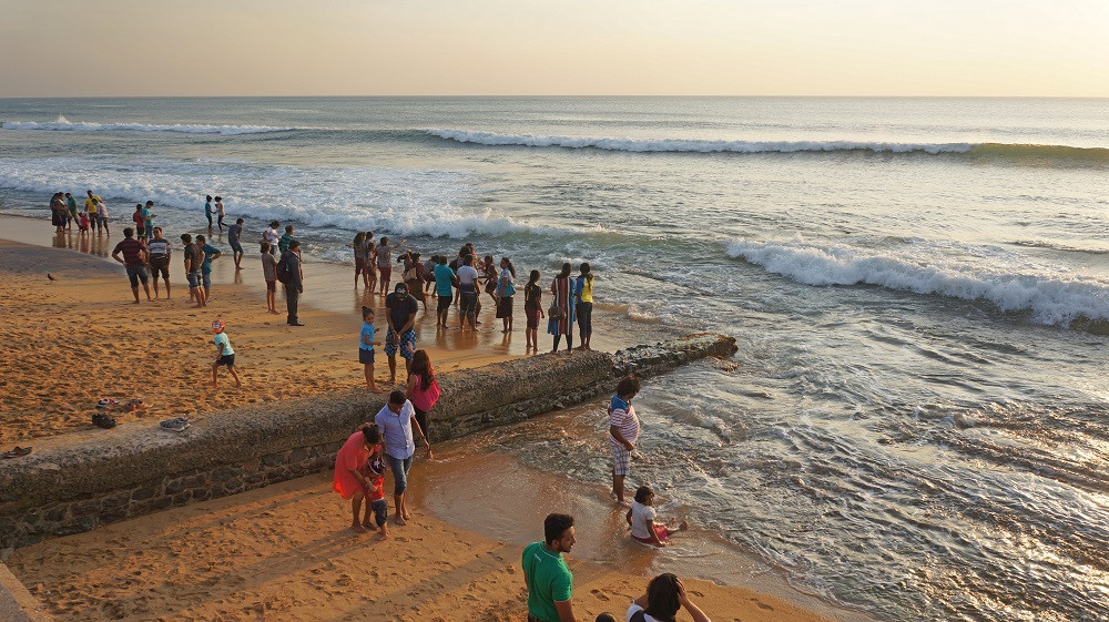Locals enjoying the sea and sand at Galle Face Green Promenade
