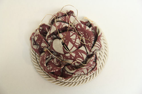 wired linen brooch on top of roped  pipping
