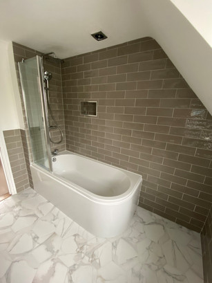 Contemporary bathroom featuring marble effect flooring and neutral metro tiles