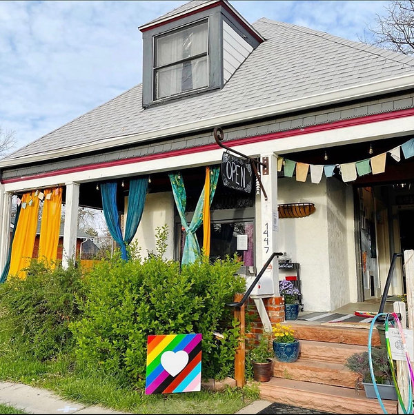 """Image of Quince Coffee House from Quince Street. White home with grey pointed roof and porch with columns and colorful curtains.. Blue skies, green grass and bushes. Signs are a pride colored rainbow and one black sign that reads """"Open"""""""""""