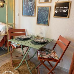 Espace repas, avec tableaux en décoration, la table et les chaises sont accompagnés d'un tapis en jute