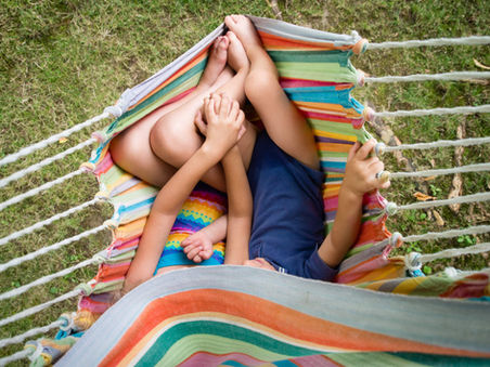 children holding hands in hammock