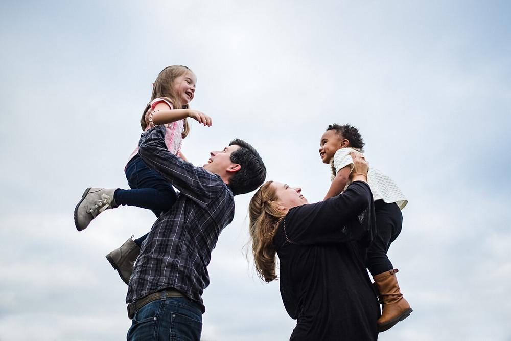 family lifting kids against the sky