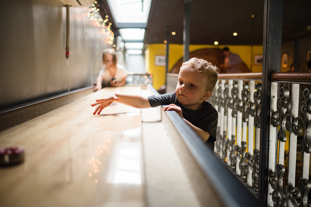 boy playing shuffle board at rybrew