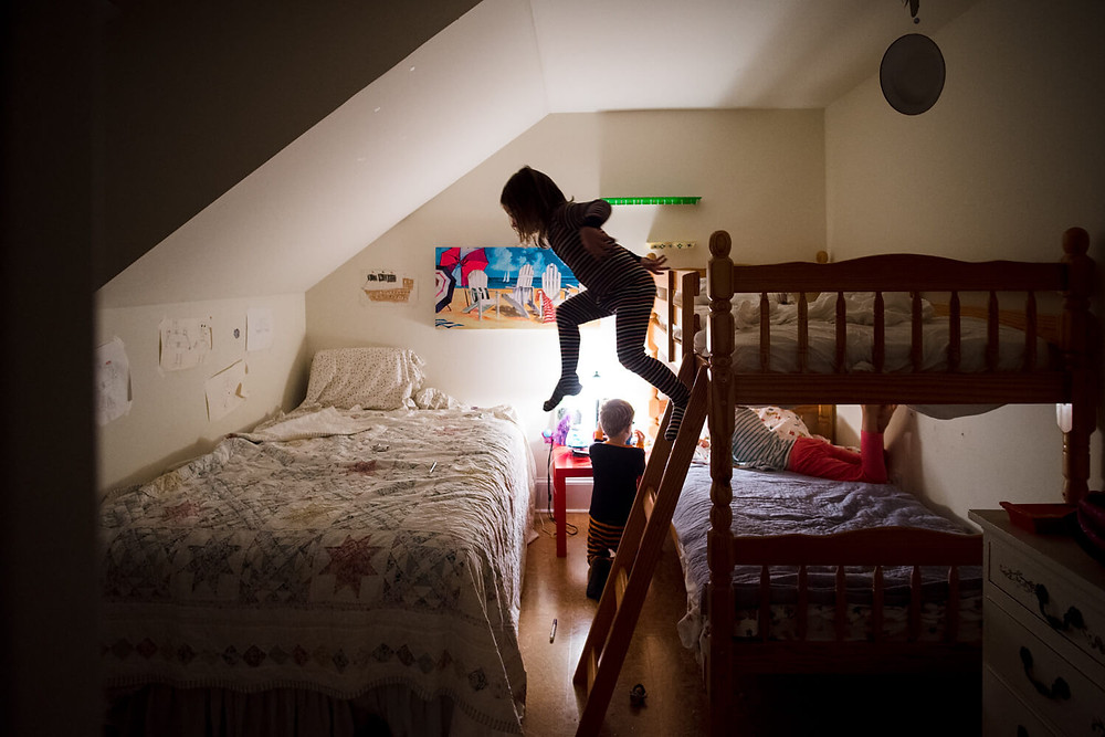 Documentary photography, silhouette of a girl jumping from bunk bed, philadelphia