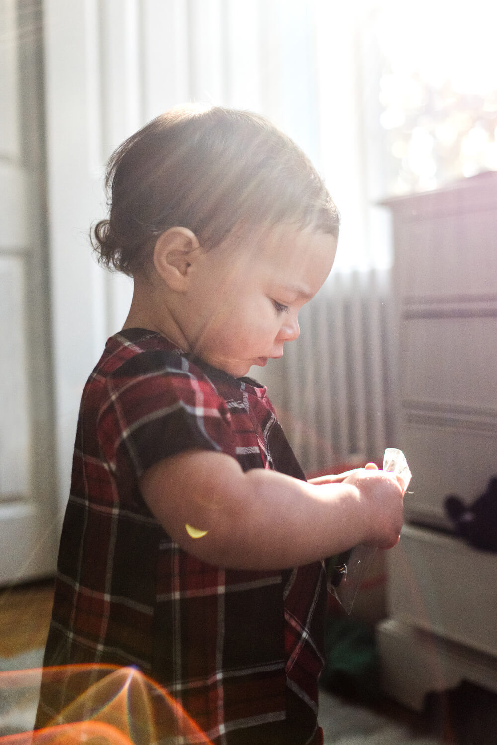 Documentary photography, profile of a toddler girl in sunflare, philadelphia