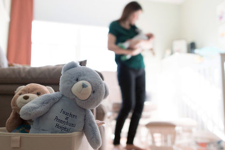 mom holding baby with teddy bear