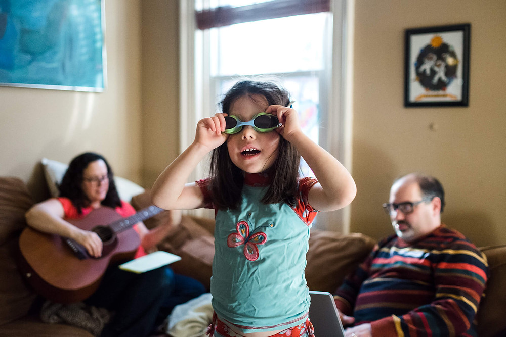Documentary photography, girl wearing goggles in her living room, philadelphia