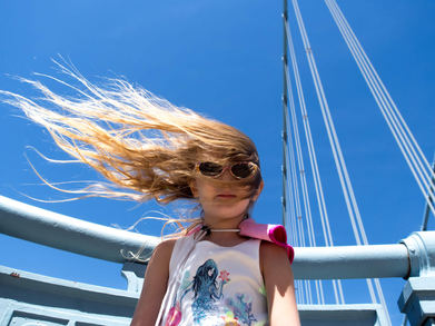 girl with hair blowing in the wind on ben franklin bridge