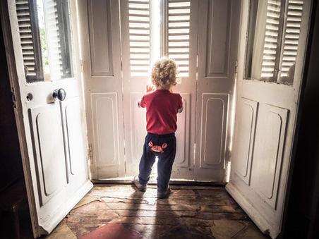 boy opening old shutters