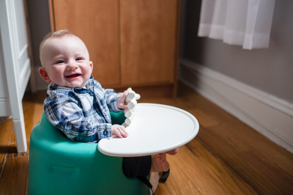 smiling baby boy in bumbo seat