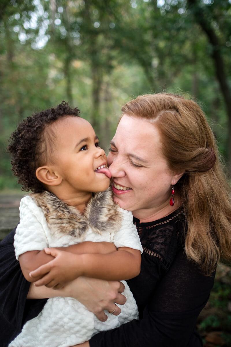 Toddler licking mother's nose