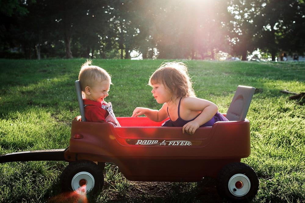 little boy and girl in radio flyer golden hour