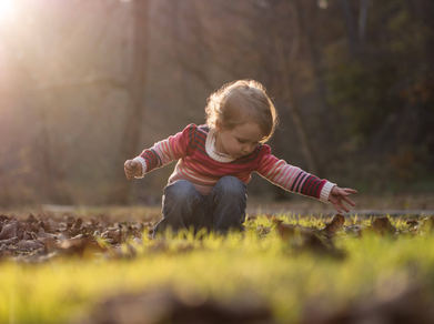 girl playing with leaves during golden hour wissahickon