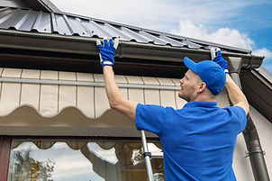 Man installing gutters on side of home