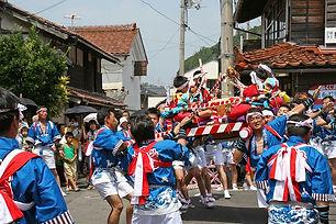 隠岐の島の伝統行事である宇屋だんじり舞風流、神輿の上に座る子供たち、それを担ぐ法被姿の男たち