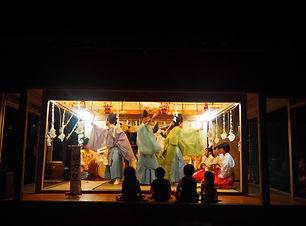隠岐の島の伝統行事である西村神楽、暗闇の中に照明があたる舞台があり、中央で舞人が舞い、左右には楽人が座る、最前列で4人の子どもが見ている