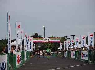 隠岐の島ウルトラマラソン、観客が声援する中、フィニッシュ地点のテープを目指して走るランナーの後ろ姿