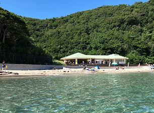 隠岐の島の塩浜海水浴場、レストハウスの後ろは青い空と緑濃い山、前に広がるのは白い砂浜と透明度の高い穏やかな海