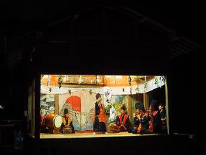 隠岐の島の伝統行事である久見神楽、暗闇の中に照明があたる舞台があり、子供の舞人が中央で舞い、左右には大人の楽人が座る