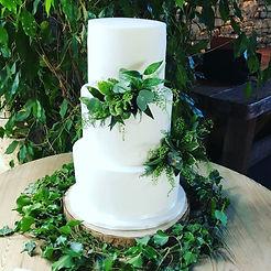 White wedding cake with green foliage