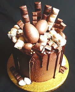 Chocolate drip cake with kinder eggs, kinder bars and kinder chocolate