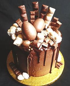 Chocolate drip cake with kinder eggs, kinder bars and kinder chocolate
