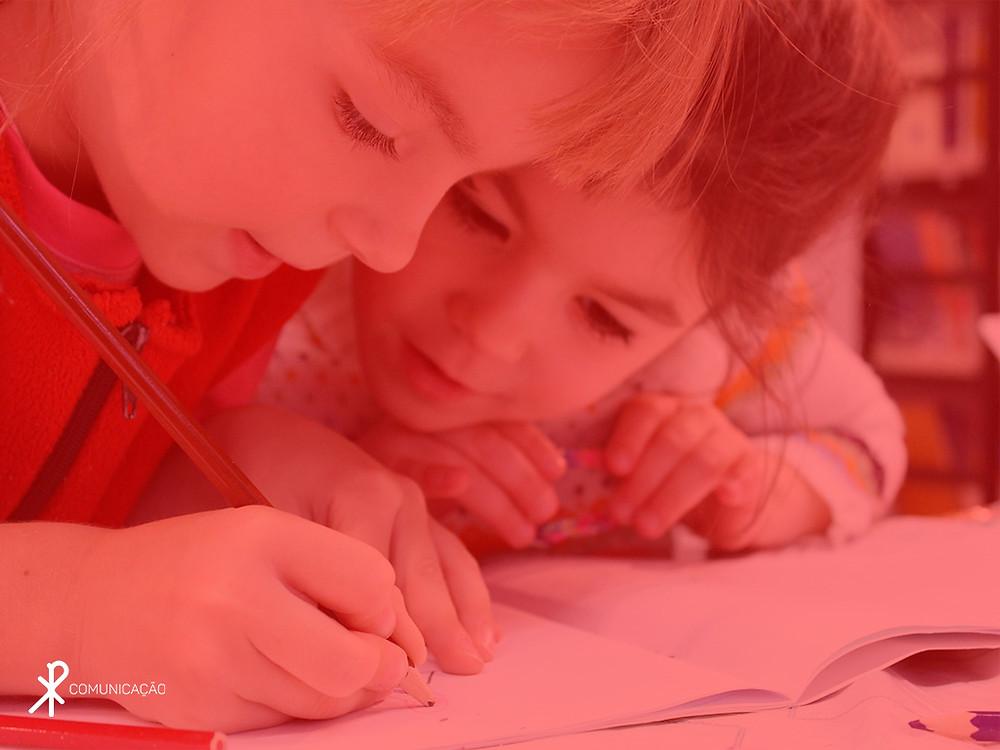 Crianças escrevendo em uma folha de papel