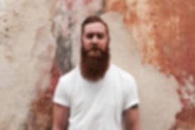 Fabrizio mit seinem orangen langen Bart vor der alten in verschiedenen orangetönen gestrichenen Mauer