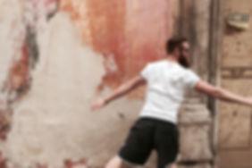 """Fabrizio mit Sonnenbrille und ausgebreiteten Armen vor alter überstrichener Wand mit verschiedenen Orangtönen, rechts alte Tür mit Aufschrift """"vendesi"""""""