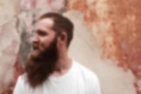 Fabrizio Gabrieli, Inhaber, weisses Shirt, oranger langer dichter Bart, Hintergrund alte überstrichene Mauer in verschiedenen orange-tönen