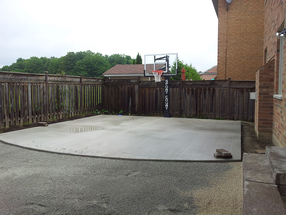 concrete base in backyard with official glass backboard basketball net