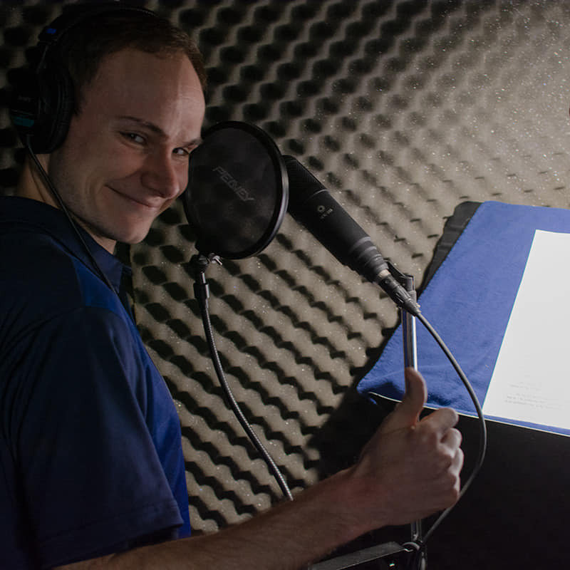 Brian Pappas giving a thumbs up in a voice acting booth