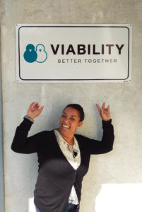 Z Gonzalez standing beneath a VIABILITY sign and pointing up at it