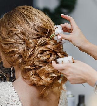 Hair stylist or florist makes the bride