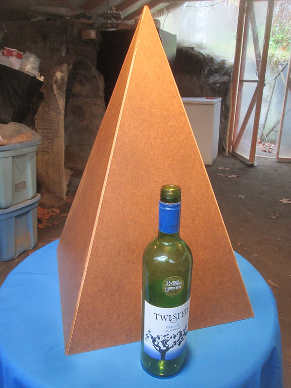 Fold-up Nubian Cardboard Pyramid with a bottle of wine in front for comparison.