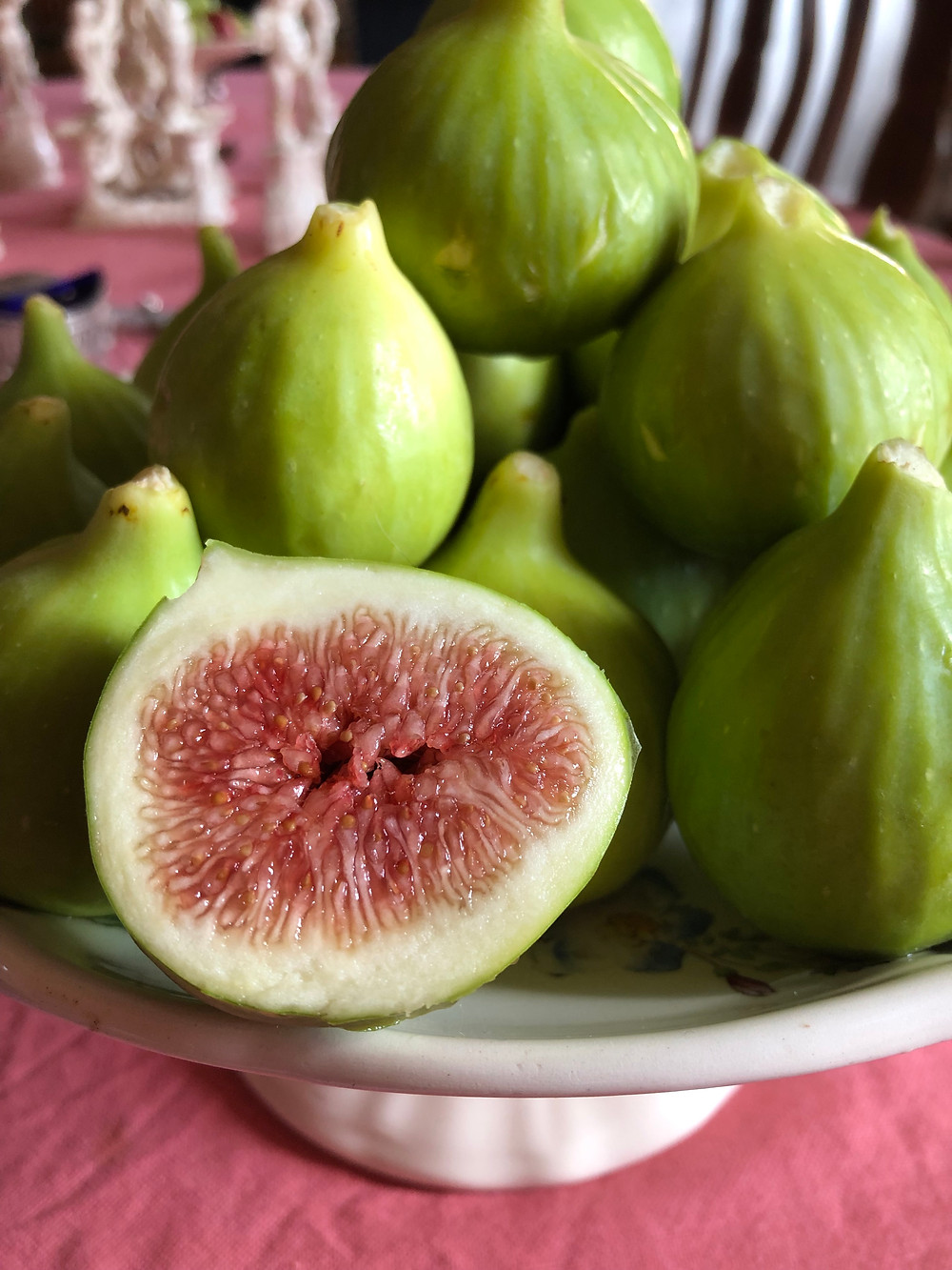 green, ripe figs, one cut in half, on a plate