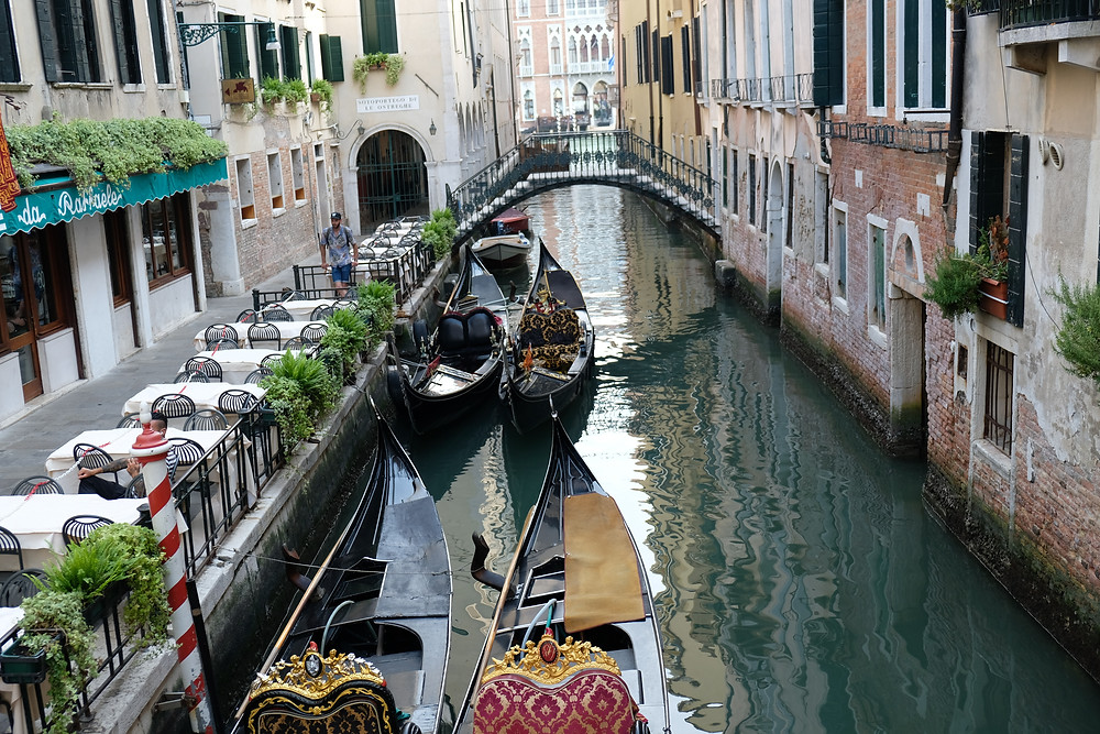 canal, bridge, and boats in Italy with dining tables along one side