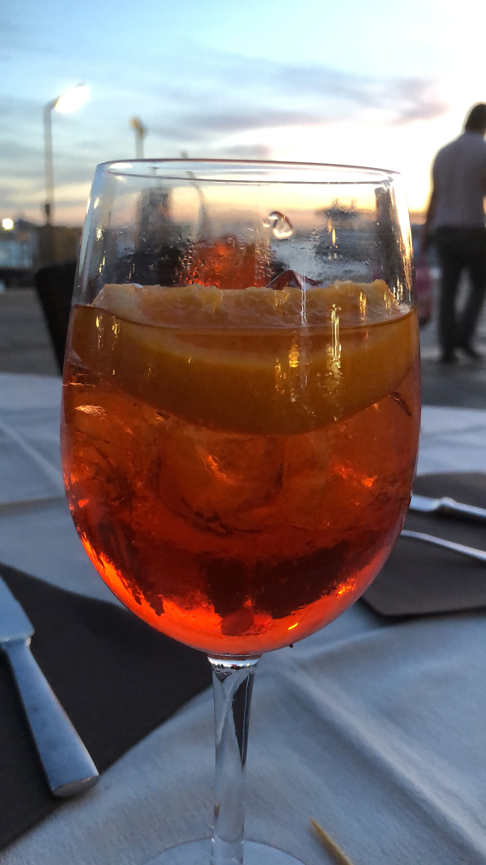 wine glass with aperol and soda on table with Grand Canal in Venice in the background