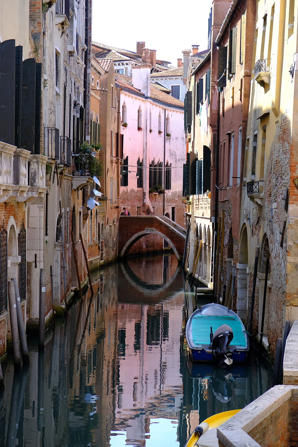 Houses in pinks, yellows and brown on either side of a canal in Venice with boats anchored in water and a pedestrian bridge.