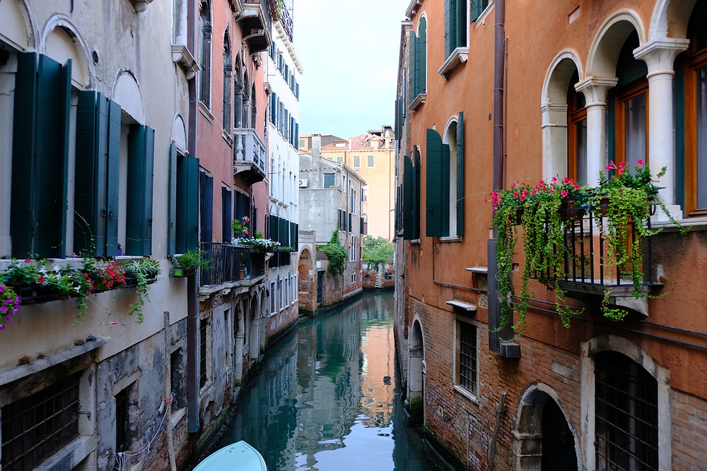 canal in venice with water in middle and colorful buildings with window boxes filled with flowers on both sides.