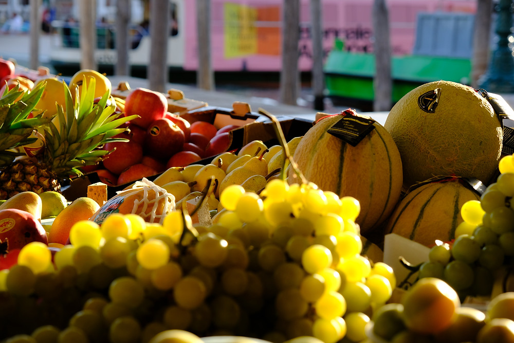 grapes, melons, pineapples and other fruit with Grand Canal Venice in background