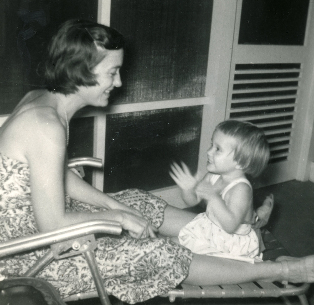 mother and daughter sitting on chair on porch