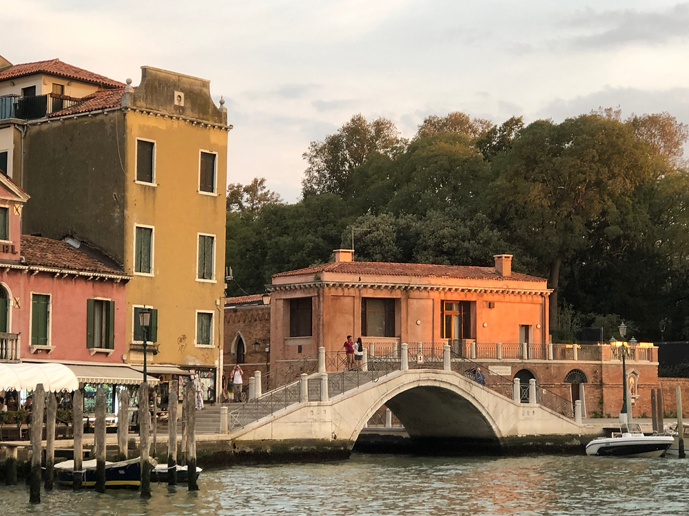 Grand canal waterfront in Venice with orange and yellow buildings and a bridge