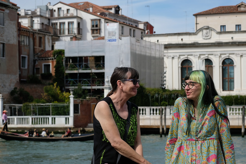 mother and adult daughter who has green hair and a flowery dress sitting on rail next to the Grand Canal